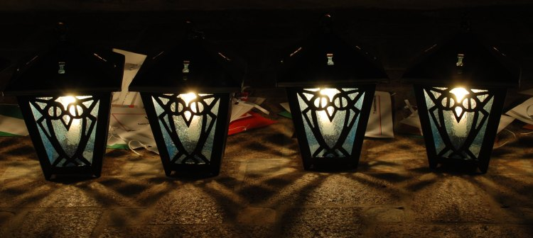 Four light blue Bryn Mawr lanterns, sitting on the ground in the darkness.